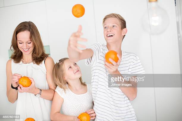 Mother and daughter studding oranges with cloves while son juggling with oranges