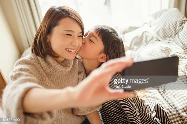 Mother and daughter taking a selfie in bed room