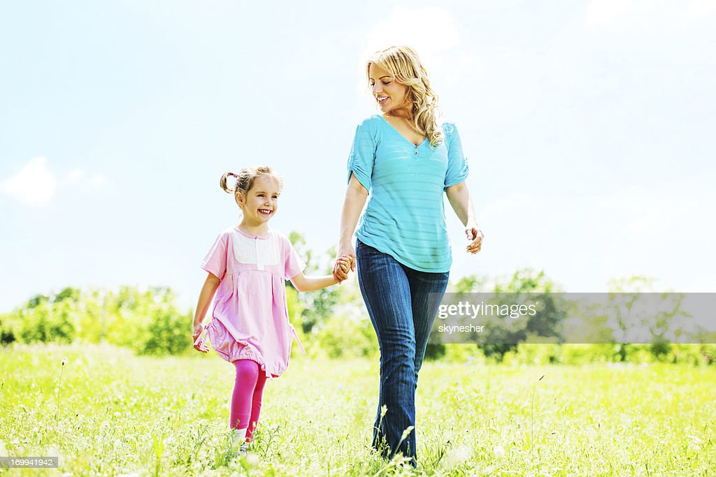 Mother and daughter taking a walk in park. : Stock Photo