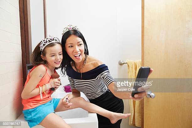 Mother and daughter taking cell phone selfie in tiaras in bathroom