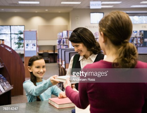 Mother and daughter (8-9) taking out books from library