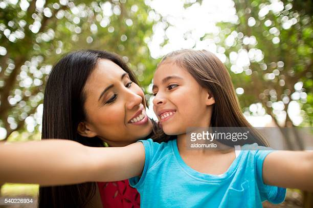 Mother and daughter taking selfie and looking at each other