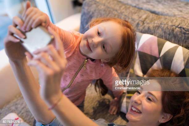Mother and daughter taking Selfie at home