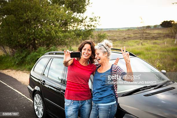 Mother and daughter taking selfie by car, Studland, Dorset