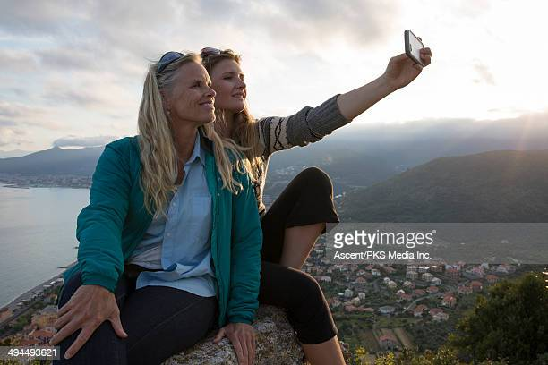 Mother and daughter taking selfie from rock
