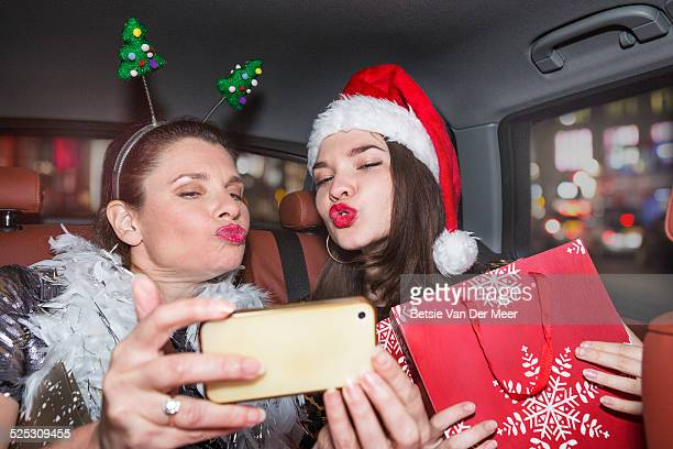 mother and daughter taking Selfie in car.