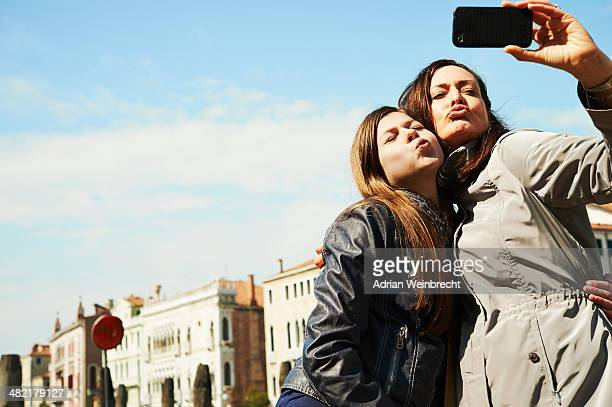 Mother and daughter taking selfie on smartphone, Venice, Italy