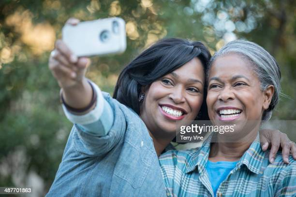 Mother and daughter taking self-portrait outdoors