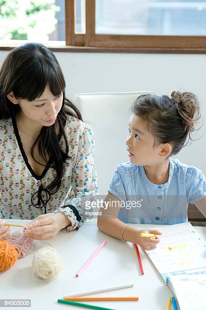Mother and daughter talking at table