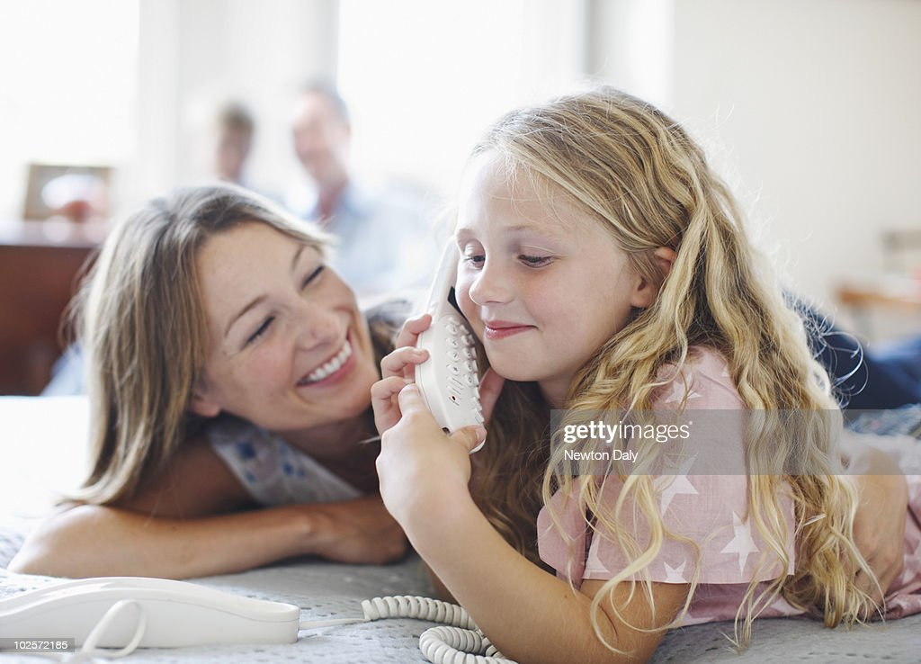 Mother and daughter (6-7) talking on telephone : Foto stock