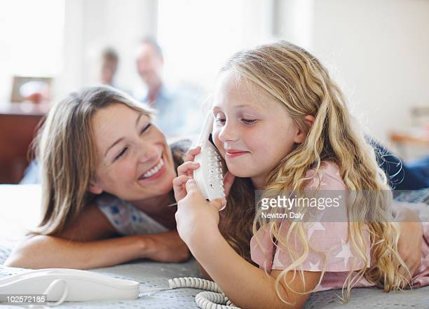 Mother and daughter (6-7) talking on telephone