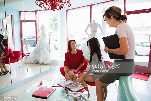 Mother and daughter talking to wedding dress designer