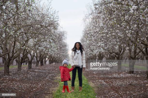 Mother and daughter together in blossom almond field.