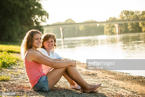 Mother and daughter together next  river