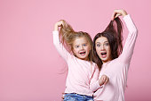 young mother and daughter having fun together on pink background
