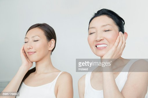 Mother and daughter touching face