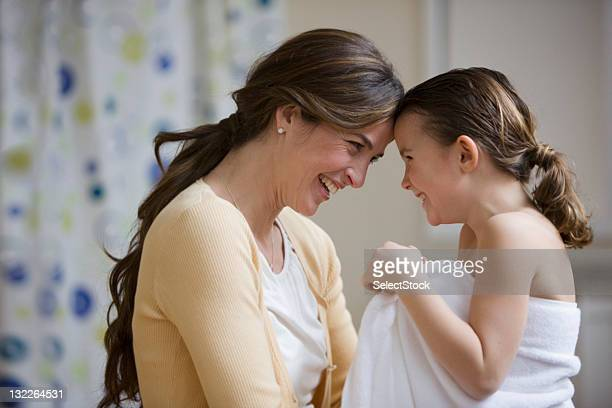 Mother and daughter touching foreheads after bath