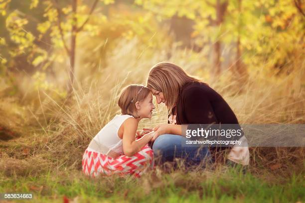 Mother and daughter touching foreheads together