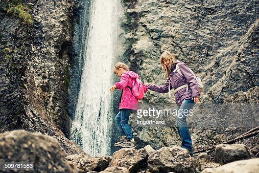 Mother and daughter trekking by the waterfall