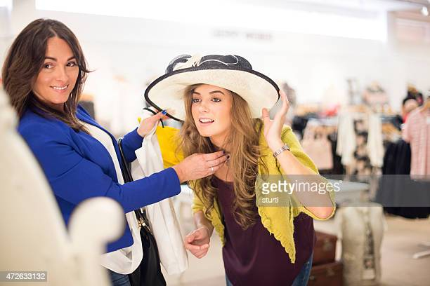 mother and daughter trying hats in a department store.