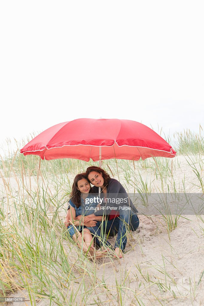 Mother and daughter under beach umbrella : Stock Photo