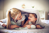 Mother and daughter under blanket at morning.