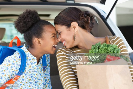 Mother and daughter unloading groceries from car : Stock Photo