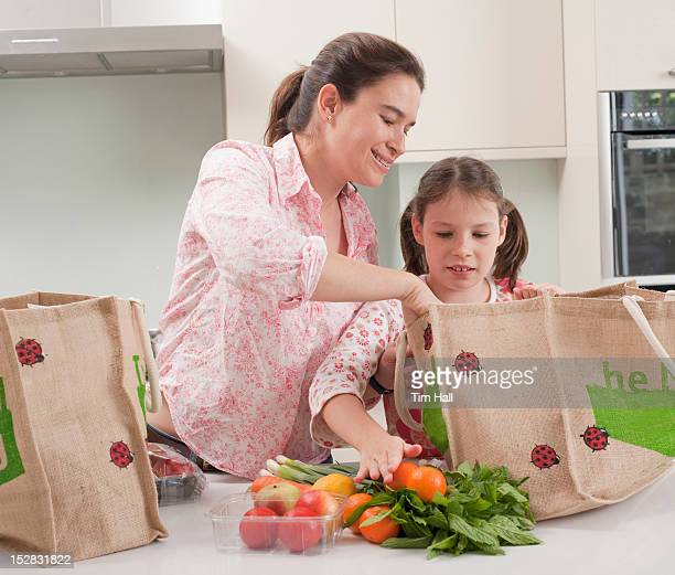 Mother and daughter unloading groceries