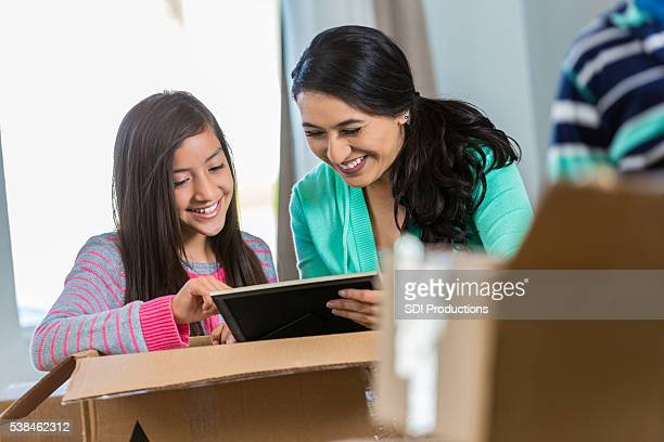 Mother and daughter unpack box in new home