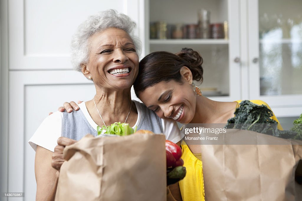 Mother and daughter unpacking groceries in kitchen : Stock Photo