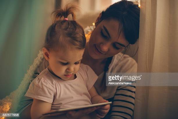 Mother and daughter using a digital tablet at bedtime