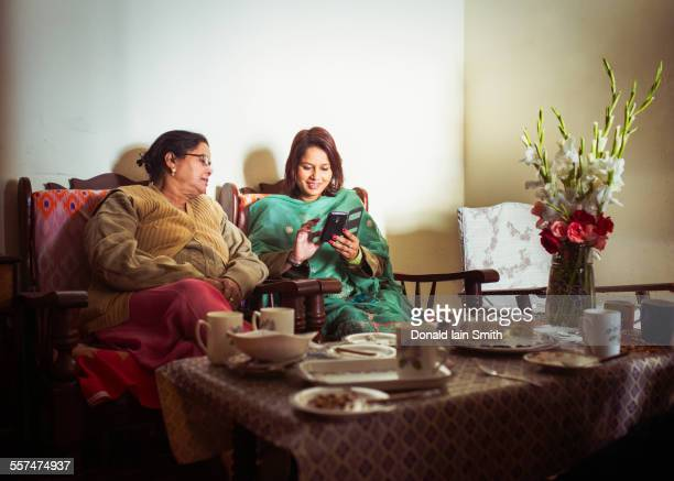 Mother and daughter using cell phone at dinner table