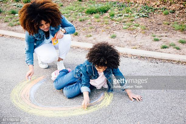 Mother and daughter using chalk to draw colourful circle on pathway