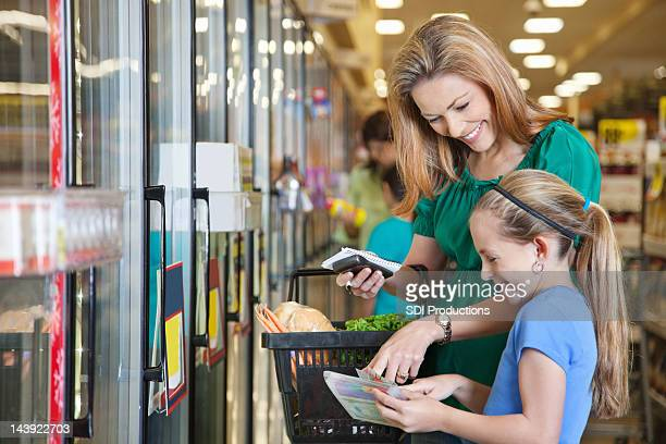 Mãe e filha com cupões na loja de mercearia