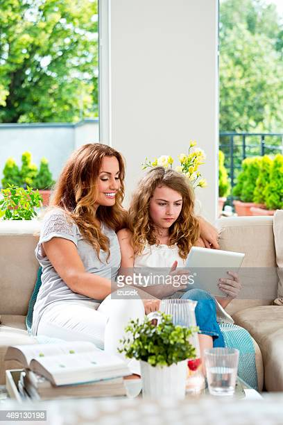 Madre e hija usando tableta digital en su hogar