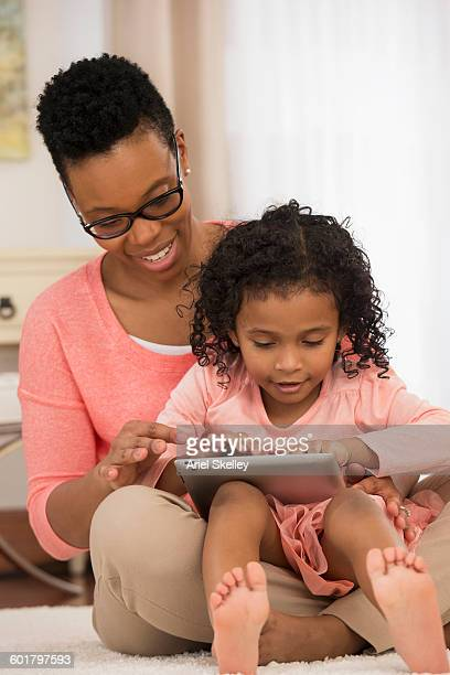 Mother and daughter using digital tablet on floor