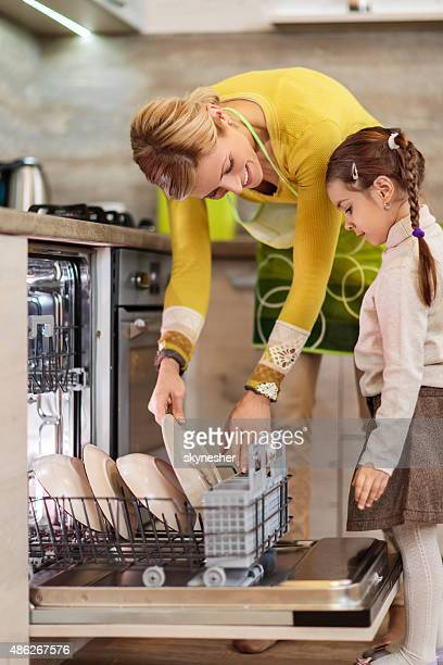 Mother and daughter using dishwasher in the kitchen.