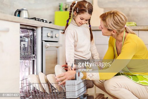 Mother and daughter using dishwasher.