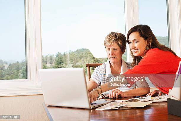 Mother and daughter using laptop at desk