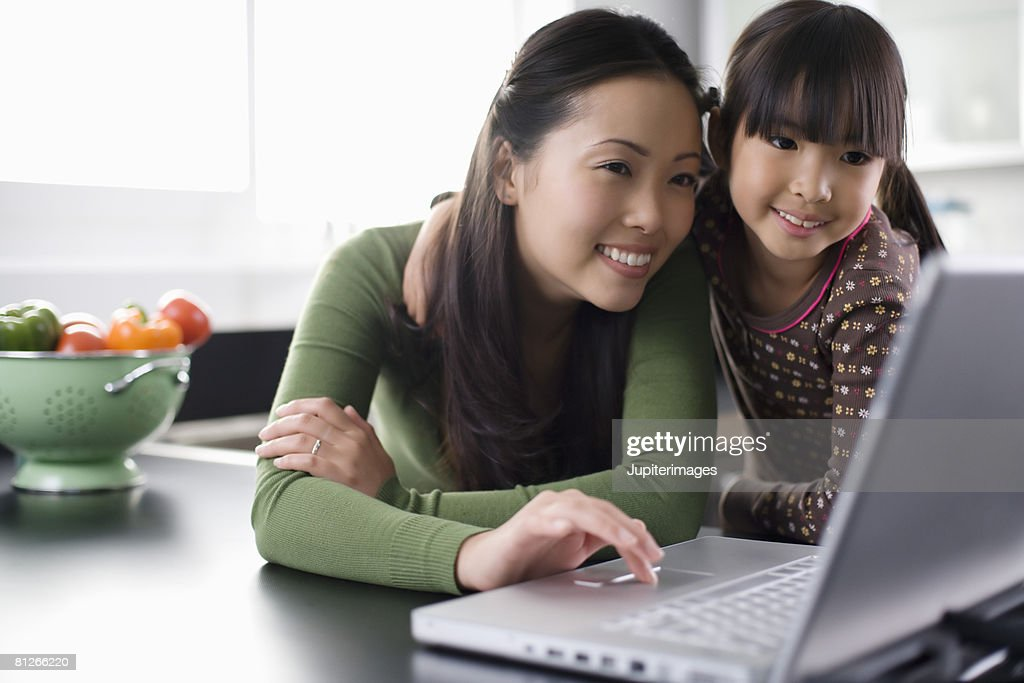 Mother and daughter using laptop computer : Stock Photo