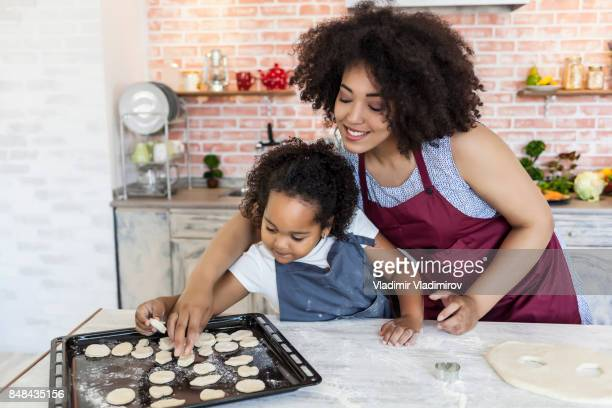 Madre e hija utilizando moldes metálicos para hacer galletas caseras