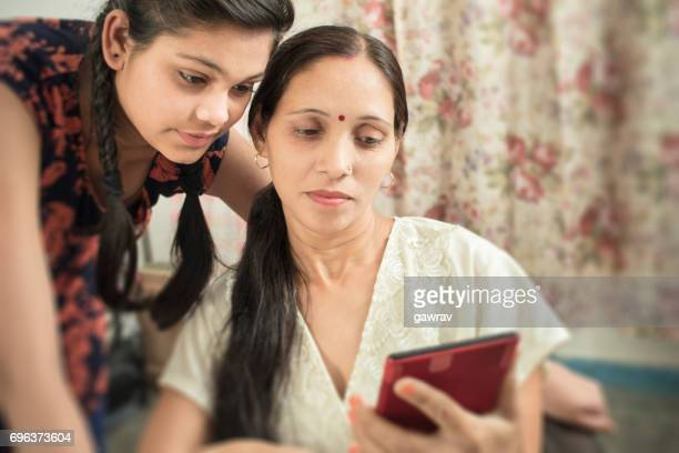Mother and daughter using phablet together in domestic room.