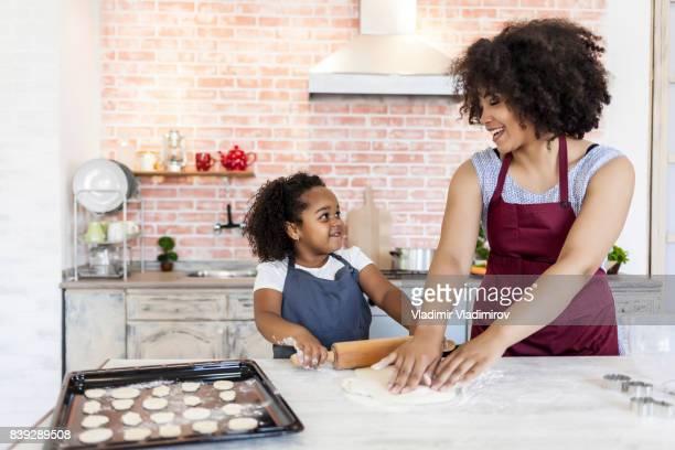 Madre e hija con rodillo y hacer galletas