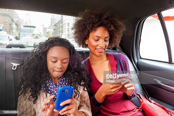 Mother and daughter using smartphones in cab