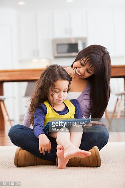 Mother and daughter using tablet computer on living room floor