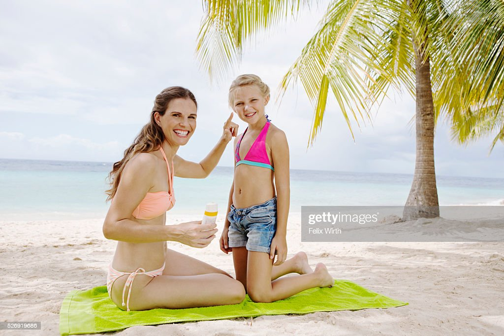 Mother and daughter (10-12) using tanning lotion on beach : Foto stock