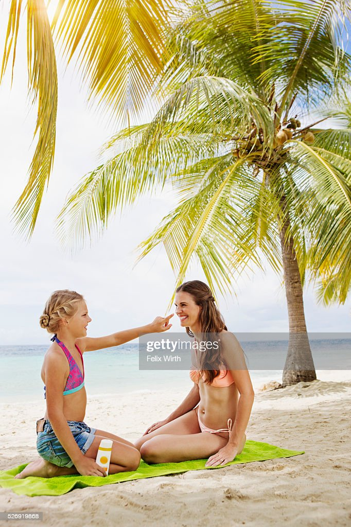 Mother and daughter (10-12) using tanning lotion on beach : Foto de stock