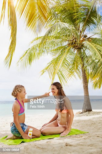 Mother and daughter (10-12) using tanning lotion on beach : Stock Photo