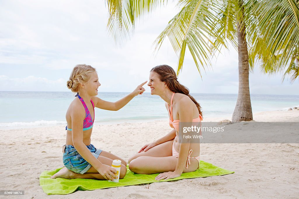 Mother and daughter (10-12) using tanning lotion on beach : ストックフォト