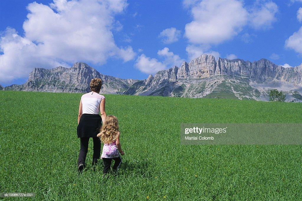 Mother and daughter (4-5) walking across alpine meadow, rear view : Stock Photo